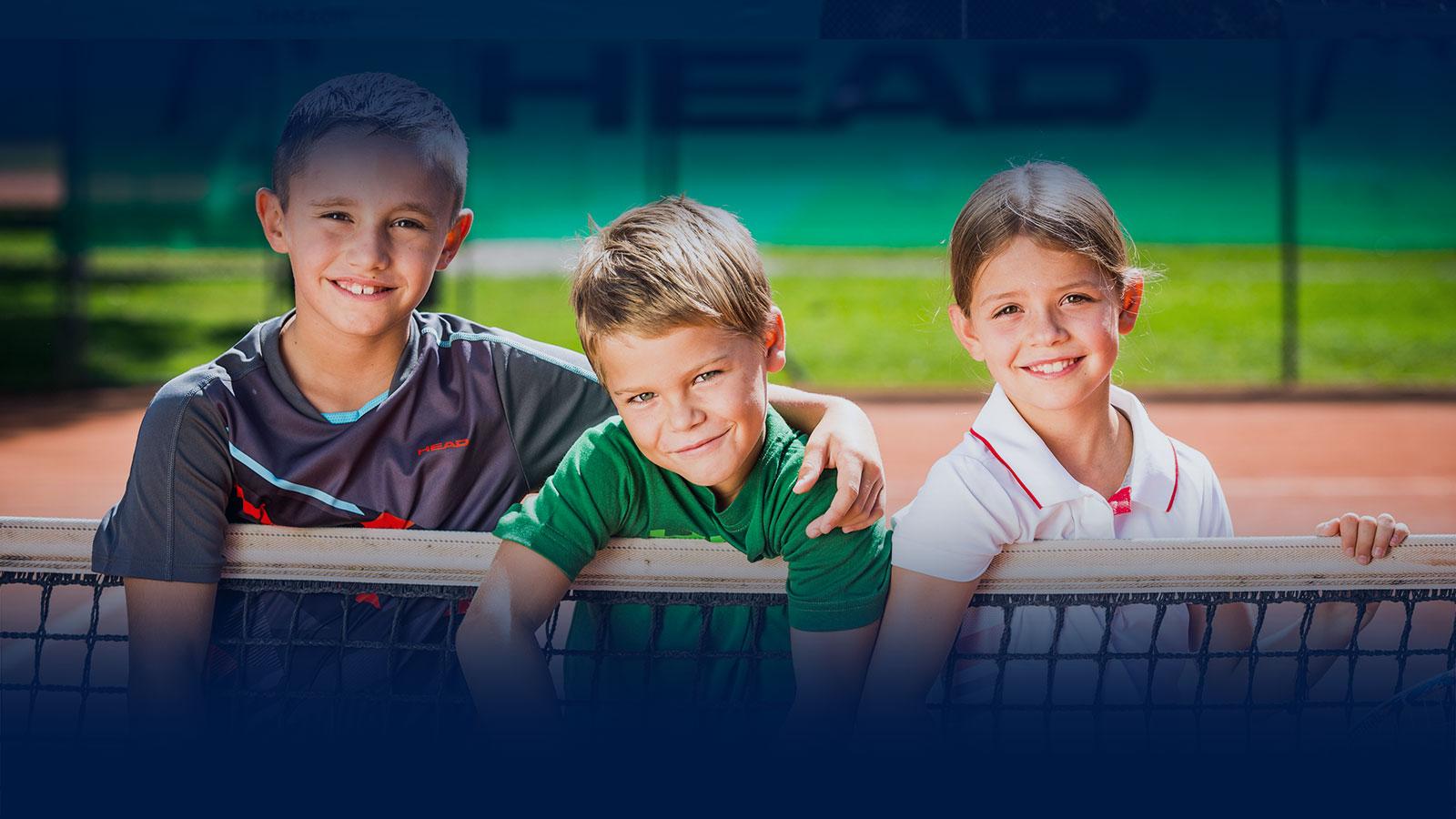 Kinder auf dem Tennisplatz sind glücklich
