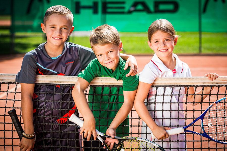 Kinder lehnen sich über Tennisnetz und halten ihre Schläger