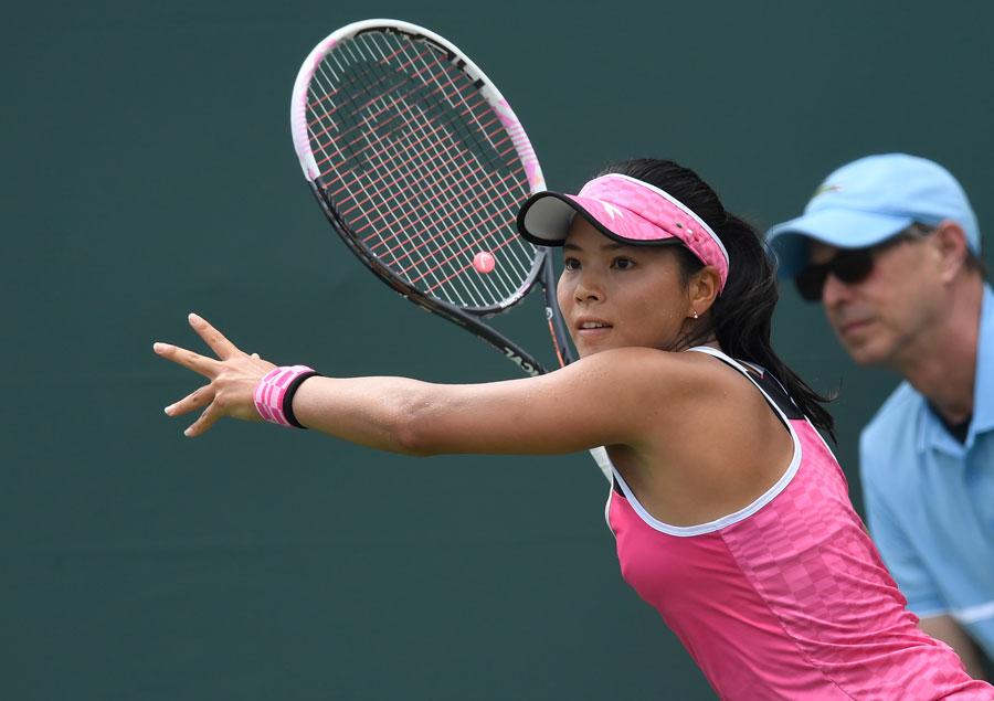 Tennis spielende Frau in pinkem Outfit
